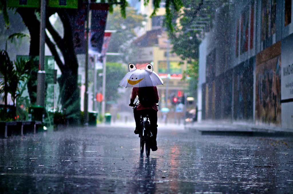 biciklis esőben esernyővel